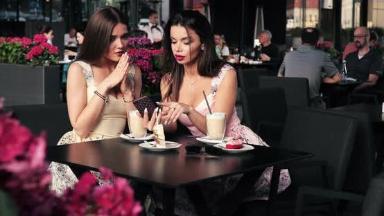 Thumbnail for Two Female Friend Sitting at Outdoors Cafe Gossiping Looking at Screen of Smartphone