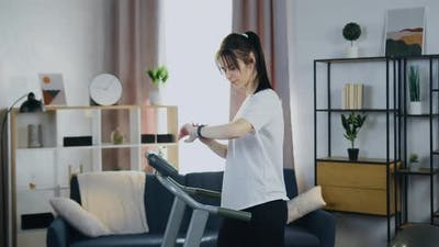 Woman Doing Running Exercises on Running Track and Configuring Program on dashboard