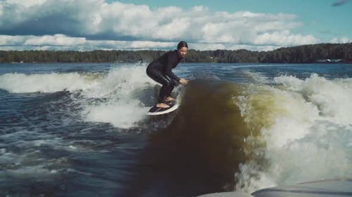 Surfing. Girl Wakesurfing in the River. Water Extreme Sport