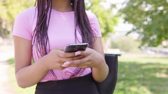 Thumbnail for A Black Woman Works on a Smartphone in a Park on a Sunny Day - Closeup