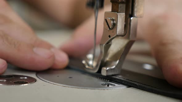 Craft Man at Work. Workshop of Making Leather Bag - Craftsman Stitches the Pouch on Sewing Machine