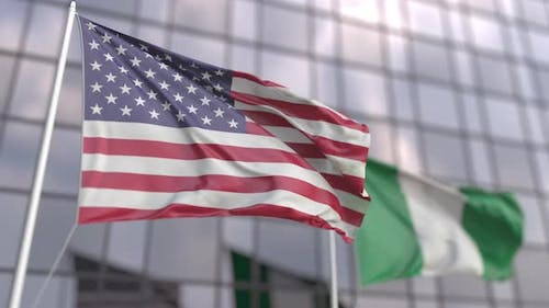 Waving Flags of the USA and Nigeria at Modern Skyscraper