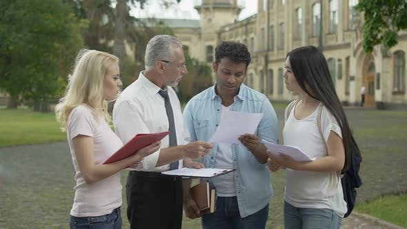 Thumbnail for Geography teacher discussing results of last test with group of students