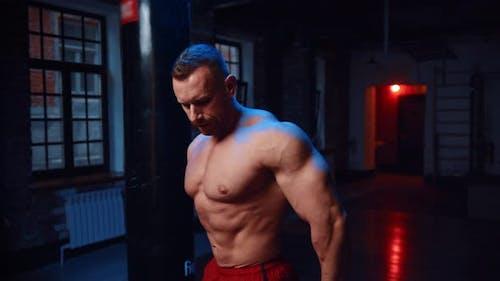 Starker Mann steht im Fitnessstudio und zeigt seine Muskeln