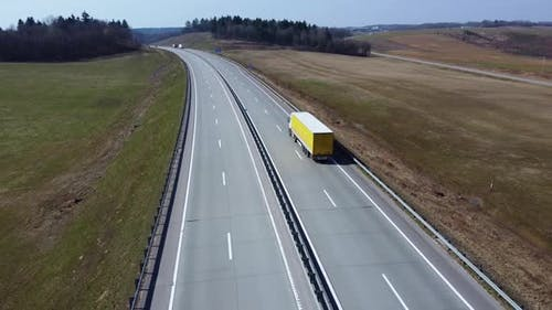 Aerial view of white semi truck with yellow cargo trailer, that moves on the highway