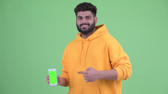 Thumbnail for Happy Young Overweight Bearded Indian Man Showing Phone and Giving Thumbs Up