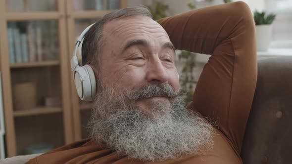Grandfather with Headphones Lounging on Sofa