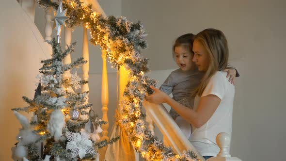 Thumbnail for Mother Shows Garland To Daughter Near Christmas Tree