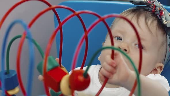 Child Plays with a Multi-colored Toy