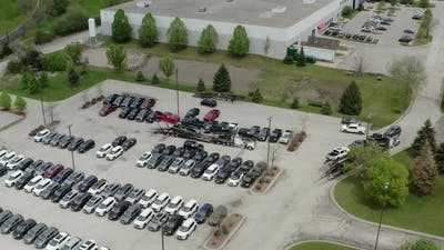 Aerial Drone View of the Car Carrier Trailer Car Hauler Loads Cars on the Trailer on Parking of the