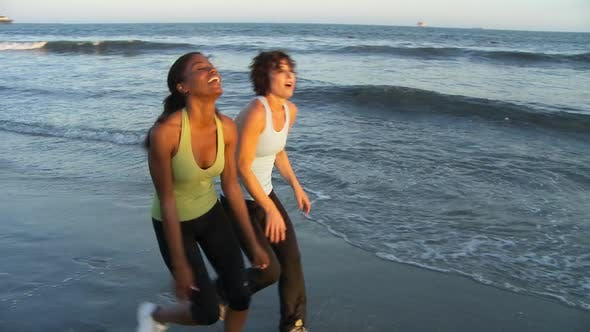 Thumbnail for Two young women catching their breath at end of run on the beach