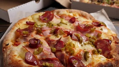 One Salami and Bacon Pizza Rotating on Boxes with Pizza Background
