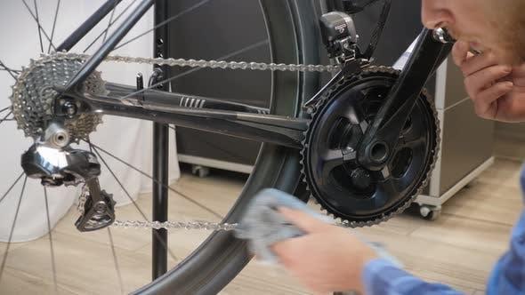 Bike maintenance. Bicycle mechanic cleaning bike chain with microfiber cloth.