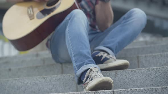 Thumbnail for Foot of Unrecognizable Guitarist Tapping Rhythm on Urban City Stairs. Male Caucasian Musician