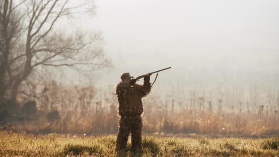 Thumbnail for Hunter in Hunting Equipment Aim the Target with Rifle in the Field