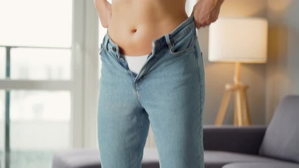 Thumbnail for Woman Puts on Jeans in a Cozy Room. The Desire To Hide Figure Flaws