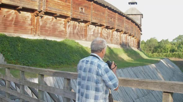 Thumbnail for Pensioner Holds Black Camera and Takes Photo in Museum Park