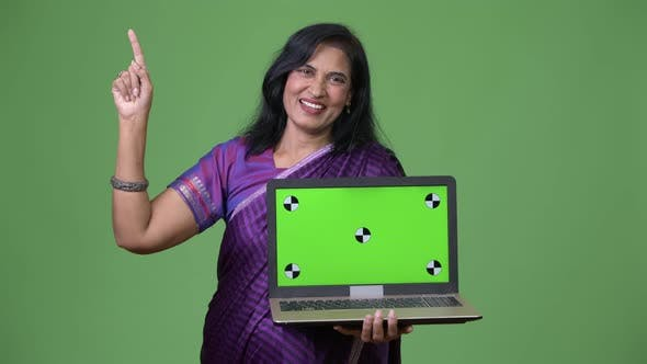 Thumbnail for Mature Happy Beautiful Indian Woman Showing Laptop and Pointing Up