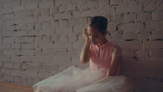 Tänzerin in einem weißen Rock sitzt an der Wand