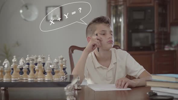 Thumbnail for Pensive Schoolboy Doing Homework Sitting at a Table at Home.