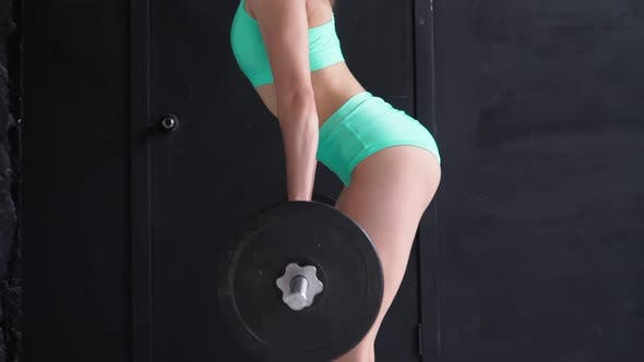 Beautiful Athletic Woman Training with Barbell. Slim Sexy Girl is engaged in Fitness and Workout.