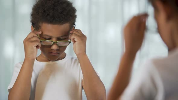 Thumbnail for Upset Afro-American Kid Putting Glasses on And Off, Eyesight Problem, Healthcare