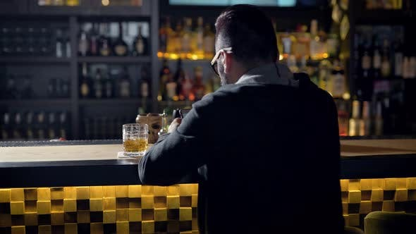 Thumbnail for Behing Shot of a Man Quietly Sitting at the Bar with Glass of Whiskey, Chatting Online