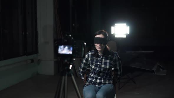 Verwandte junge Frau Geisel mit einer Augenbinde vor einem Kameraobjektiv