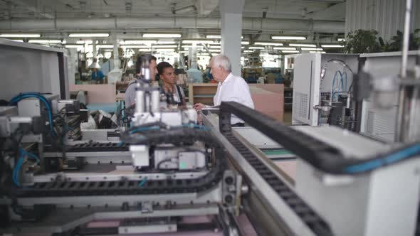 Thumbnail for Workers Discussing Automated Machinery
