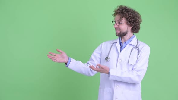 Thumbnail for Happy Young Bearded Man Doctor Showing Something and Giving Thumbs Up