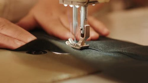 Hand of the seamstress is using white industrial sewing machine sew zipper