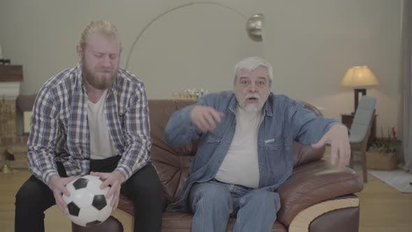 Thumbnail for Portrait of Disappointed Caucasian Father and Son Watching Soccer Match Indoors. Adult Man and