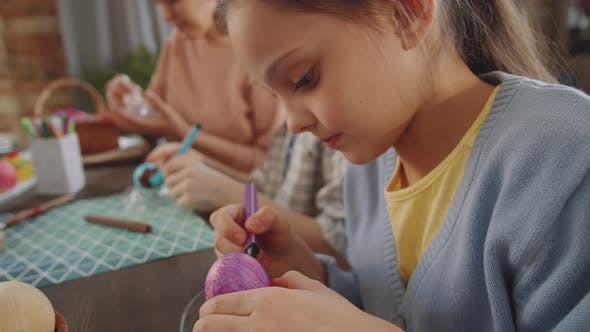 Pretty Girl Drawing on Easter Egg with Marker Pen