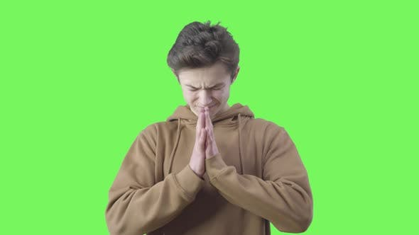 Desperate Boy Praying at Green Background. Portrait of Teenage Brunette Caucasian Believer with