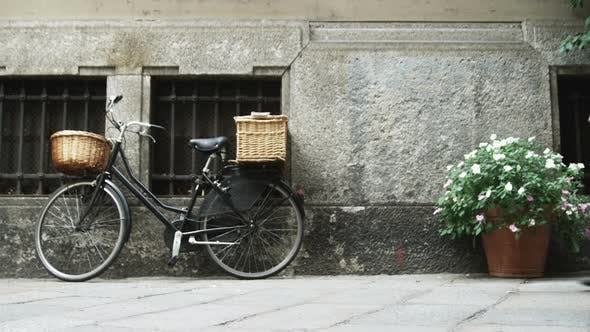 Bicycle and flowers next to a building in Milan Italy.