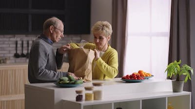 Elderly Married Couple is Unpacking Bag with Food at Home Kitchen Pair of Retirees is Putting Food