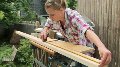 Woman measuring wooden plank with tape measure