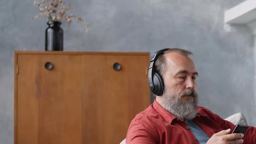 Retired Man Listening to Audio Book at Home