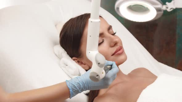 Woman at Beauty Clinic Receiving Facial Treatment