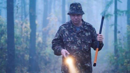 Brutal Mann mit einer Axt und eine Taschenlampe geht durch den Wald