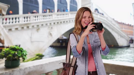 Thumbnail for Happy woman tourist in Venice taking picture with camera