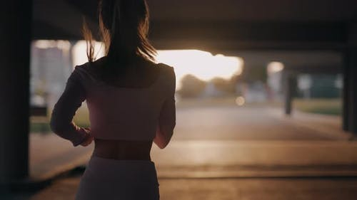 A Young Woman Runner is Training in the Summer Within a City