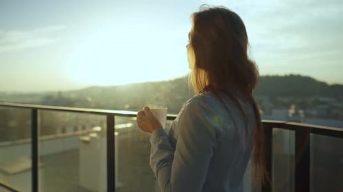 Pretty Woman Drinks Cup of Coffee or Tea, Watching a Beautiful Urban View and Enjoy Relax Breathing