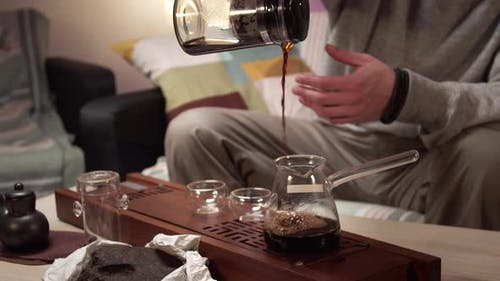 An Unknown Man Pours Brewed Tea From a Teapot Into a Jug, From a Jug Into a Glass Bowl and Drinks