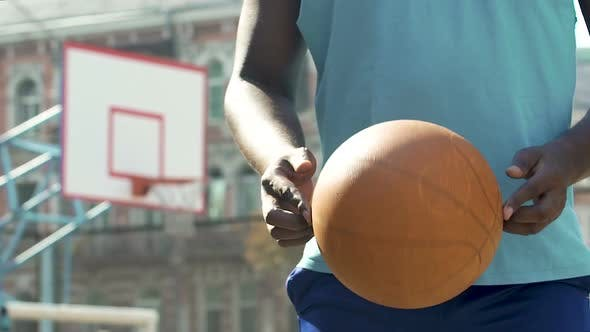 Cover Image for Professional Basketball Player Holding Ball, Encouraging Young People for Sports