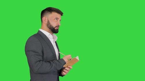 Business Man Writing Down Ideas on a Green Screen, Chroma Key.