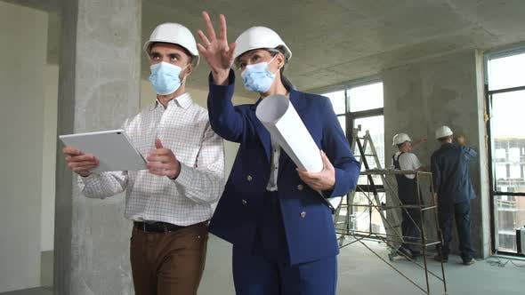 Masked Designers Discussing Apartment Renovation