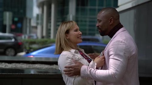 A African-Americanman and a White Woman Laugh and Smile on the Street in the Background of a