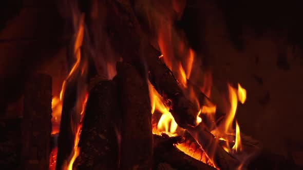 Burning wooden logs in fireplace. Fire in fireplace with logs and flames.