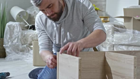 Thumbnail for Concentrated Man Assembling Wooden Shelf